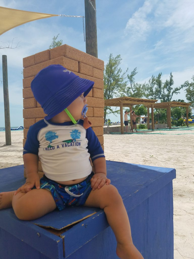 A baby sitting in the shade on the beach next to a giant Jenga set.