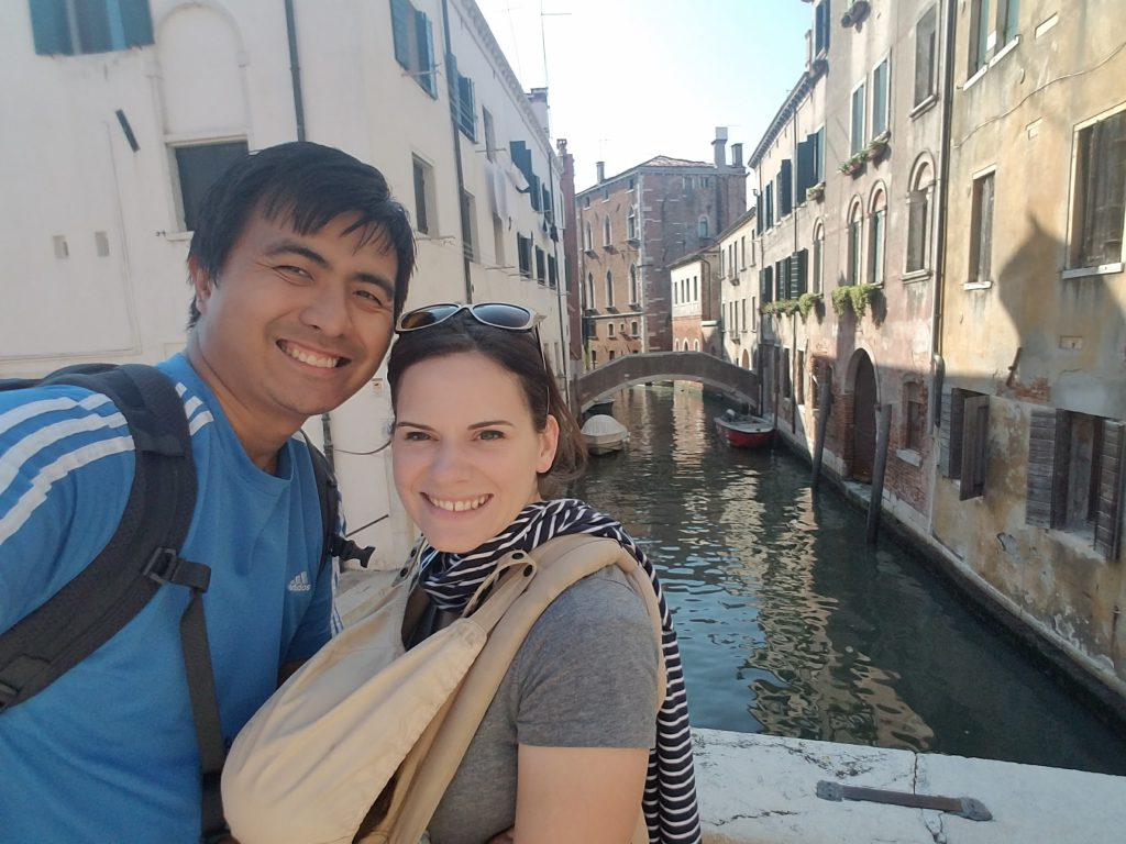 Man and woman in front of a canal in Venice, woman is wearing a sleeping baby in a baby carrier