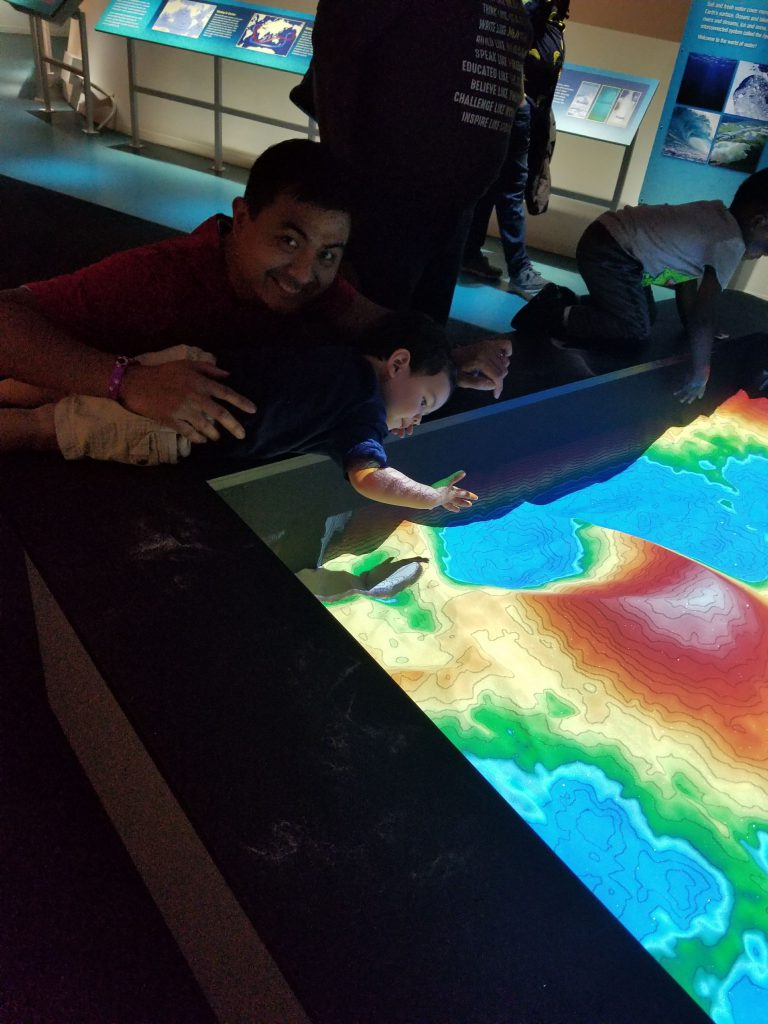 A man and a toddler looking at a topographic map at a museum.
