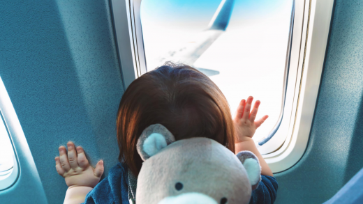 Young child looking out the window on an airplane