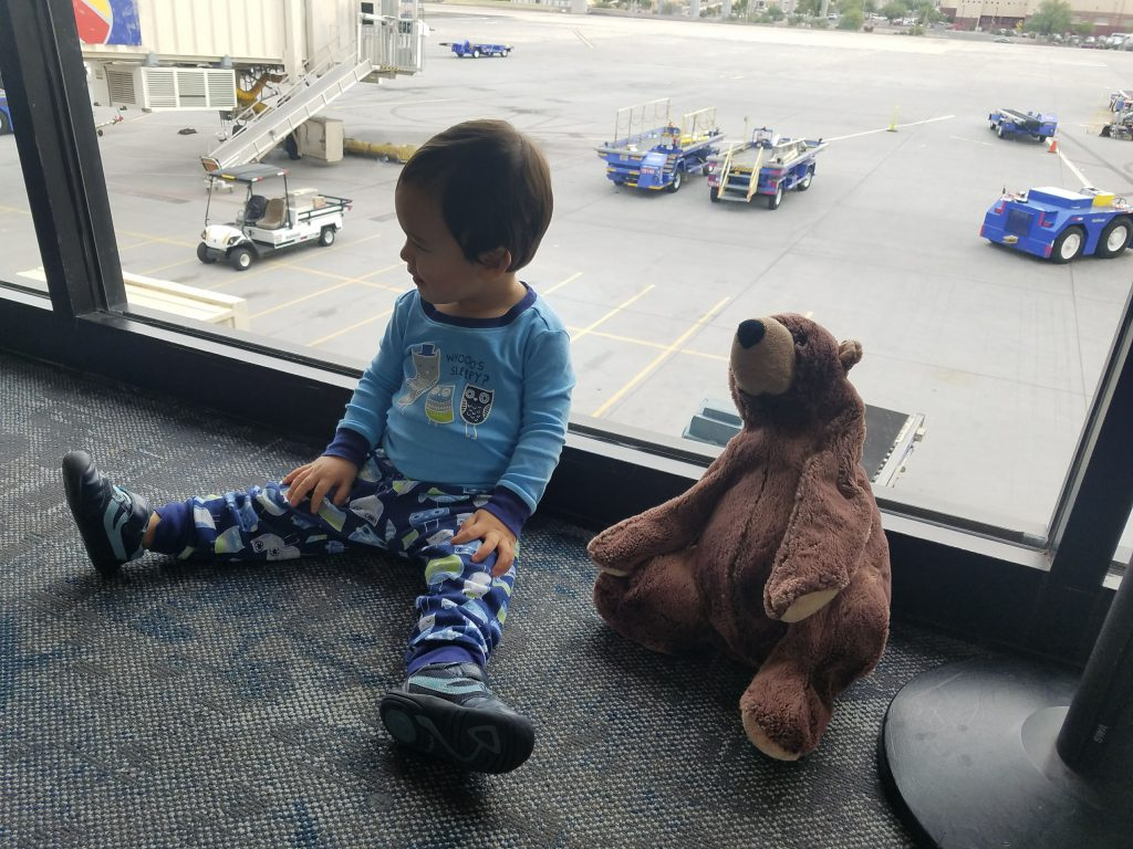 Toddler and his stuffed bear sitting by an airport window