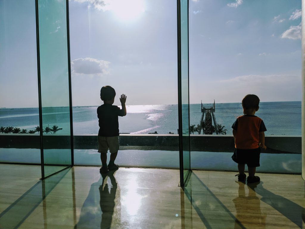 Two children looking out a window at a sunny sea.  Sunshine helps fight jet lag in babies and toddlers.