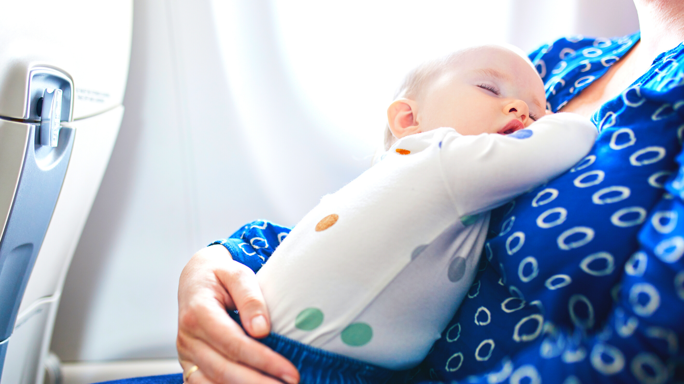 Baby sleeping on mom on a plane
