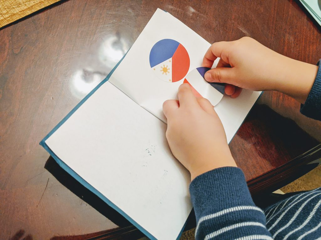 Putting a French flag in the passport at the end of the France preschool unit