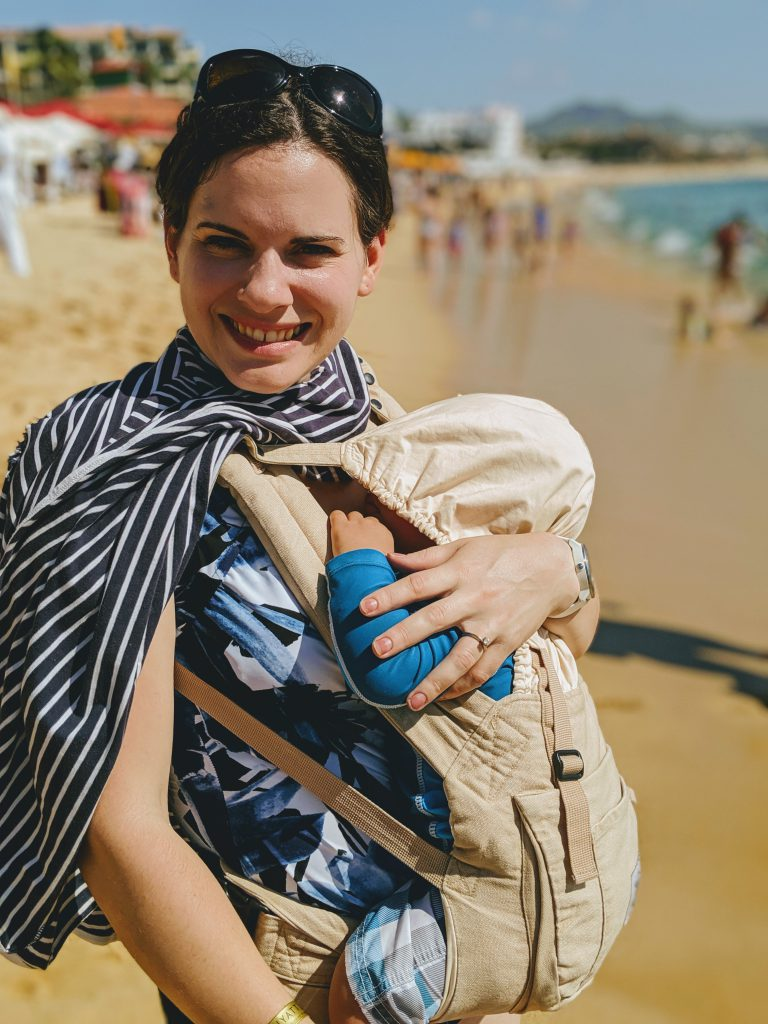 Baby taking a nap in a baby carrier on the beach