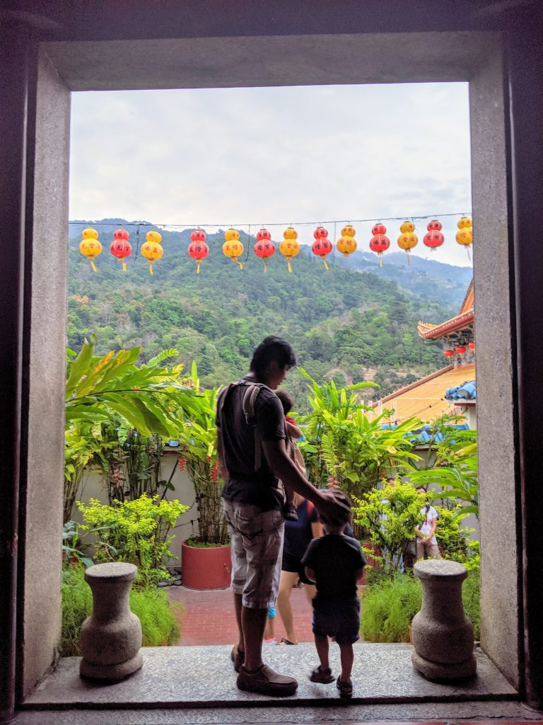 Man and two children standing in a doorway at Kek Lok Si Temple in Penang, Malaysia