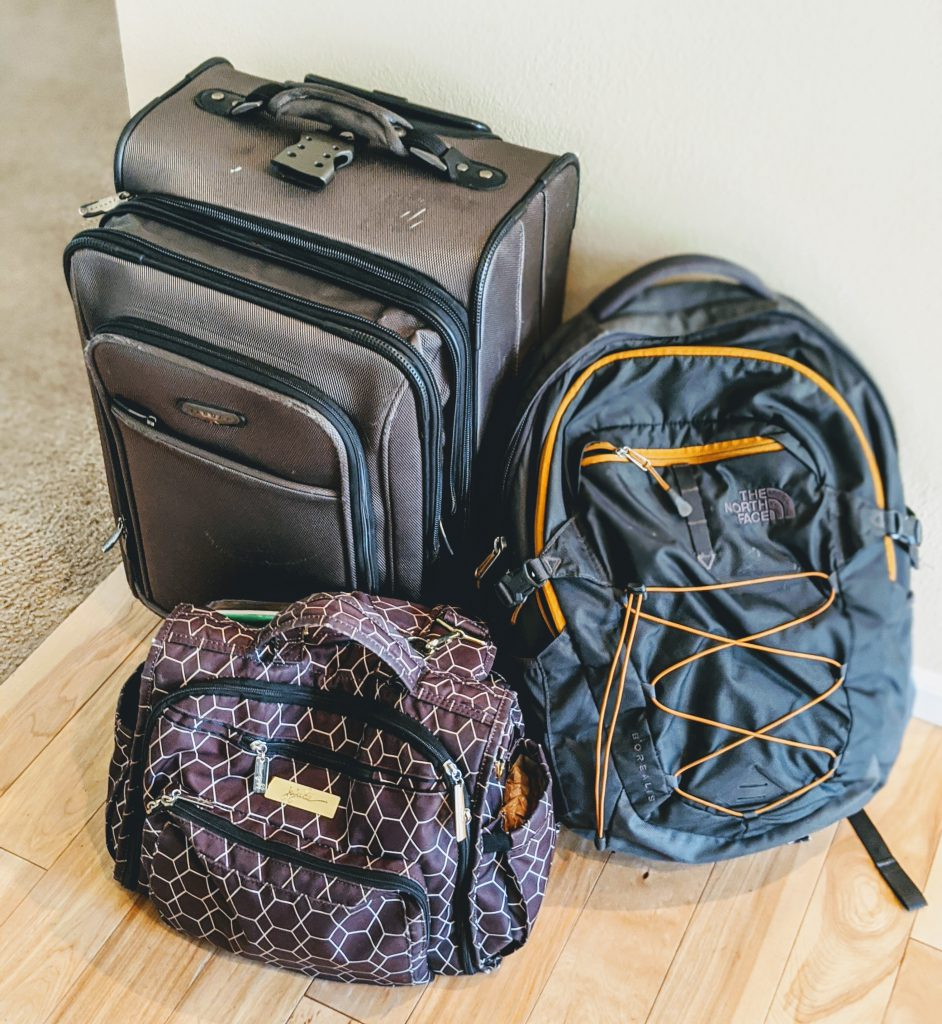 A suitcase and two backpacks for packing light on a trip to Italy with a baby