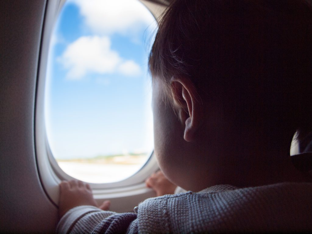 Toddler looking out a plane window