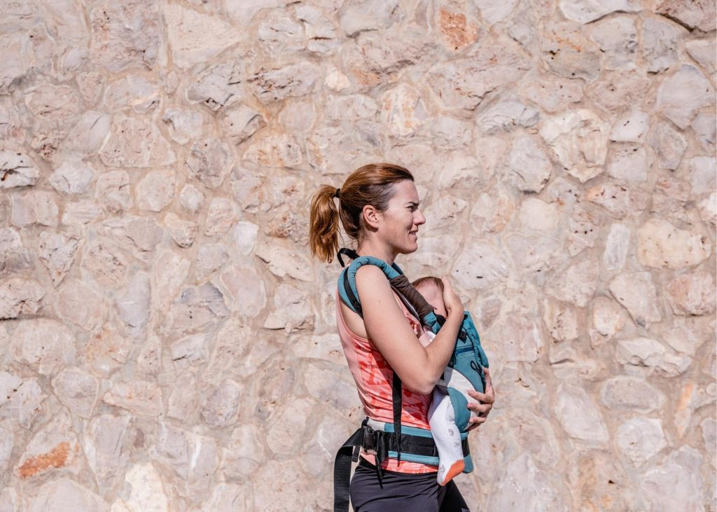Woman walking with a baby in a baby carrier