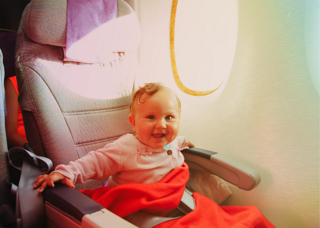 Baby sitting on an airplane seat smiling