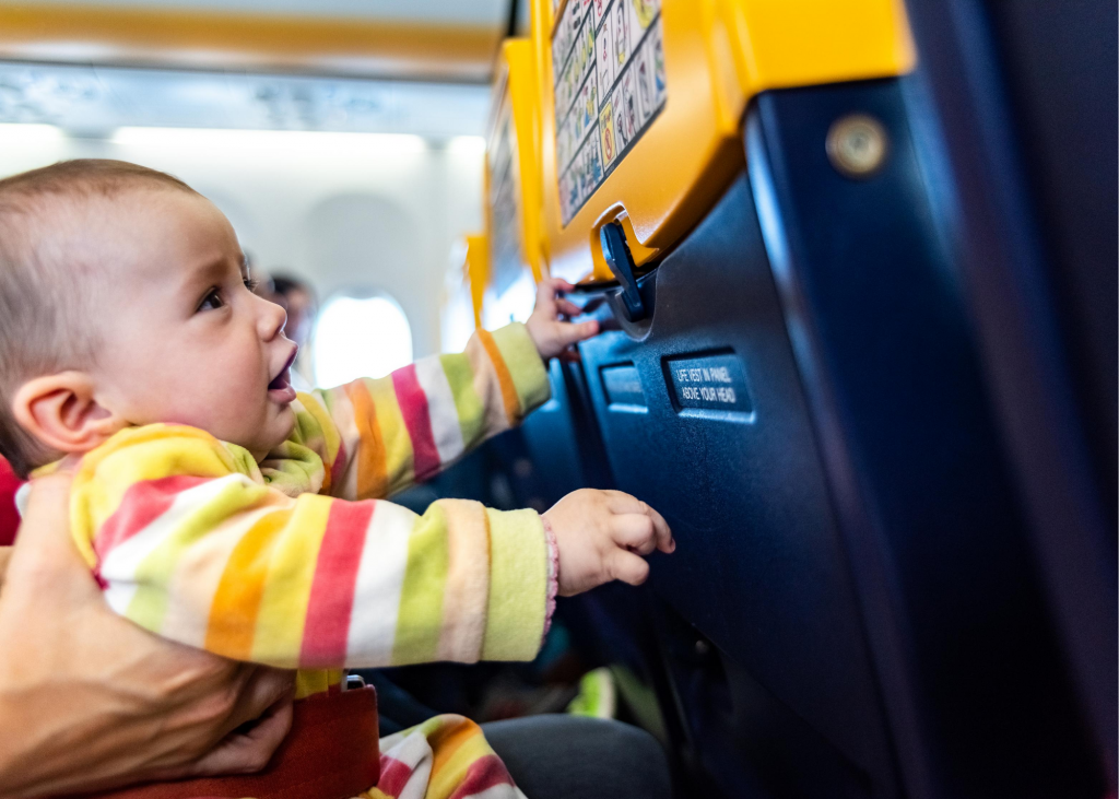 Baby on a plane playing with the seat back