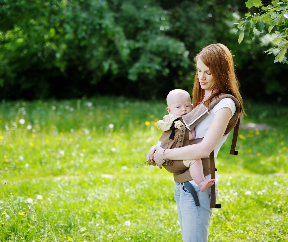 Woman wears a baby in a baby carrier