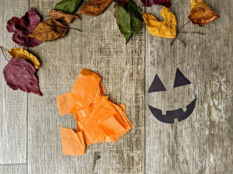 Cut out orange tissue paper and a pumpkin face for the jack-o'-lantern from black construction paper