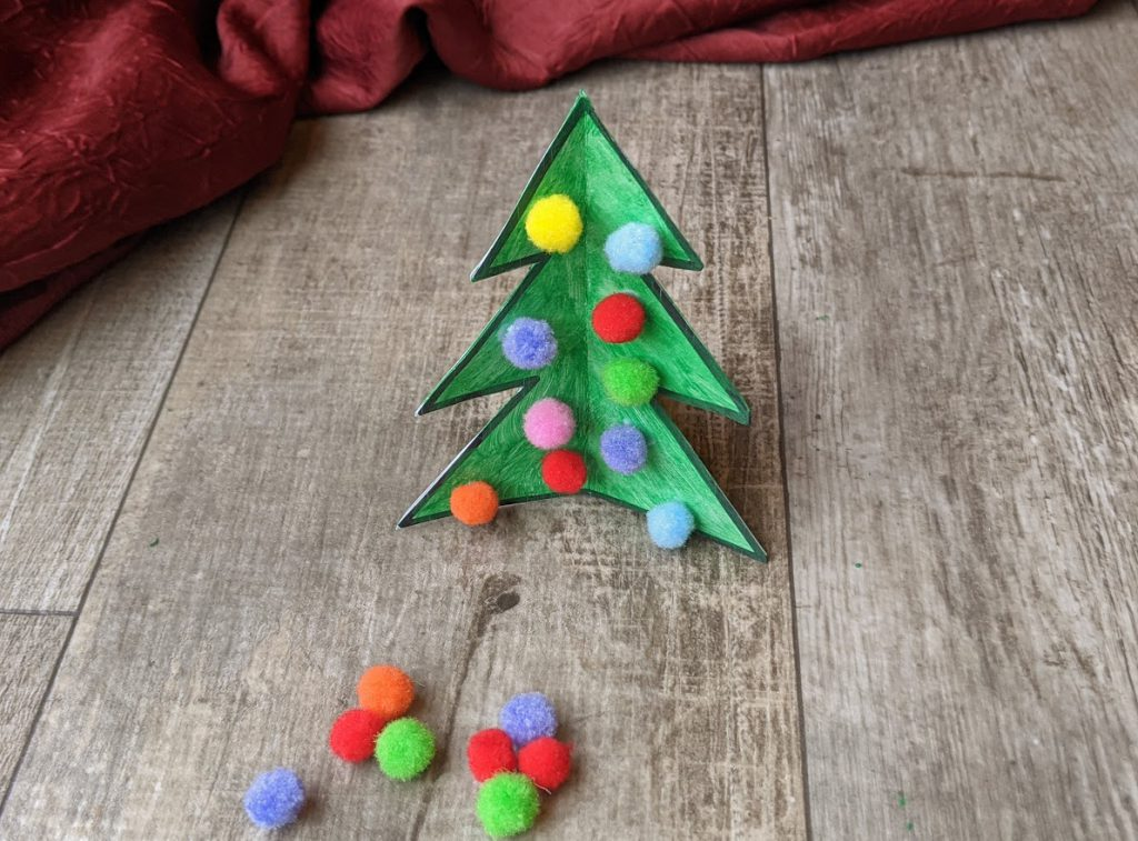 Add pom poms to complete the Christams tree craft