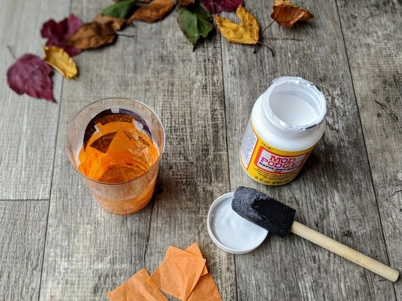 Continue painting the inside of the cup with Mod Podge and putting tissue paper on it.