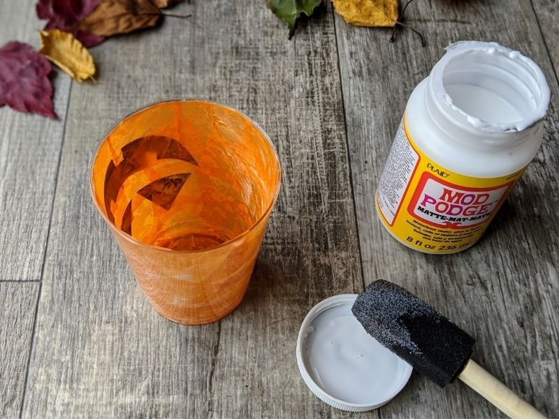 Jack-o'-lantern cup craft completely covered in tissue paper on the inside