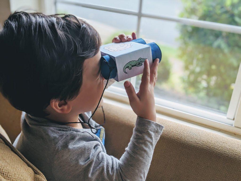 Boy looking through the completed binoculars kids craft