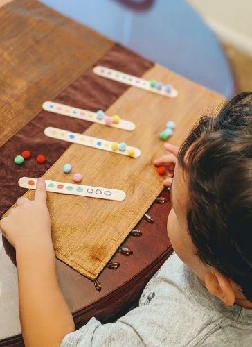 Preschool child completing the pattern sticks