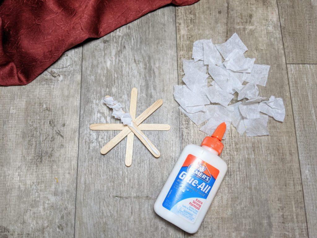 Glue crinkled tissue paper onto the popsicle sticks