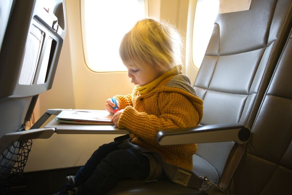 Toddler on an airplane drawing in a book