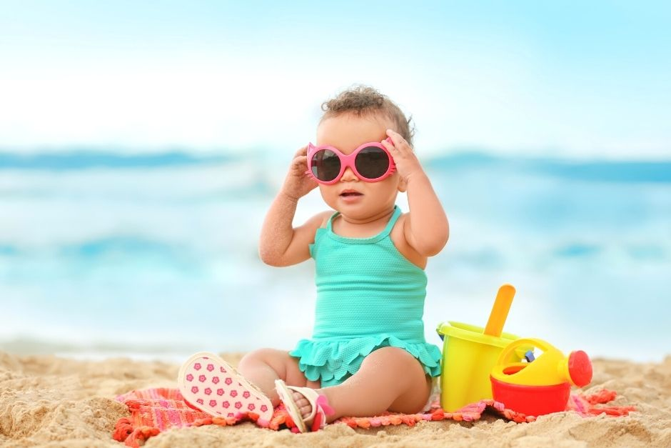 Toddler on the beach wearing sunglasses- beach essentials for toddlers and babies