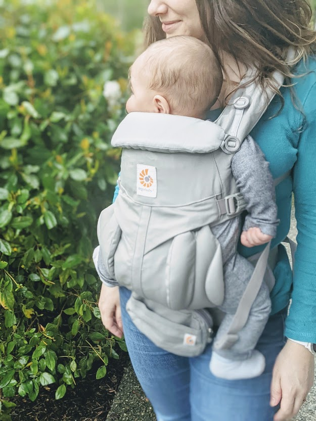 Baby in an Ergobaby Omni 360 carrier- a carrier is one of our top baby travel essentials