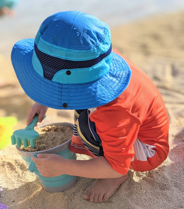 Child playing in the sand- beach essentials for toddlers and babies