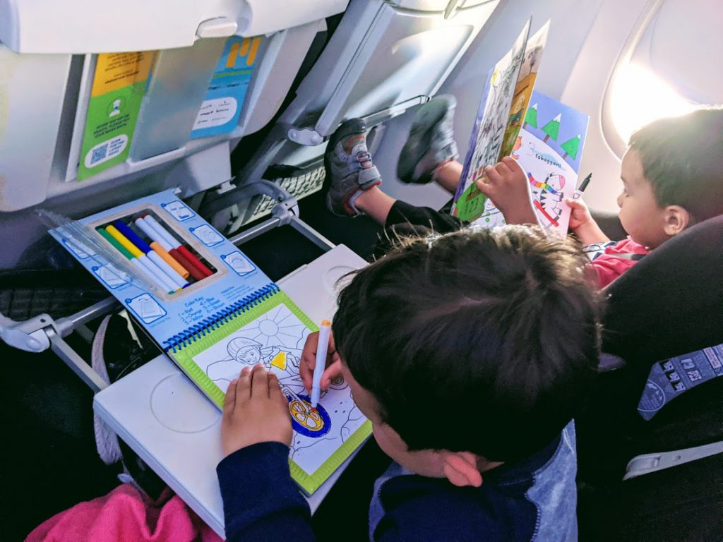 Two children drawing in books on a plane- how to entertain a toddler on a plane