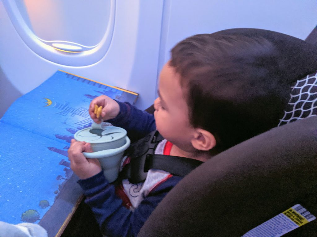 Toddler entertained on a plane eating a snack from a snack catcher