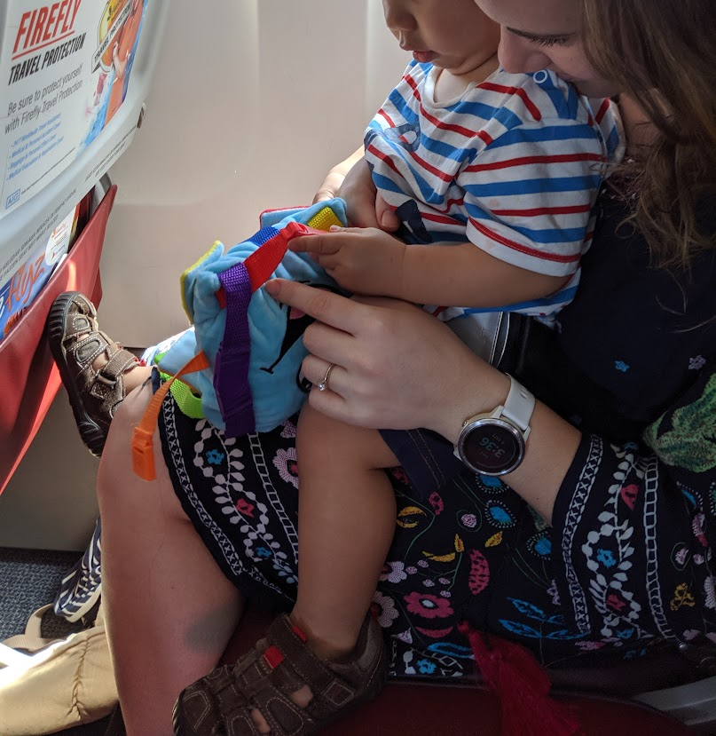 Child playing with a buckle toy on a plane