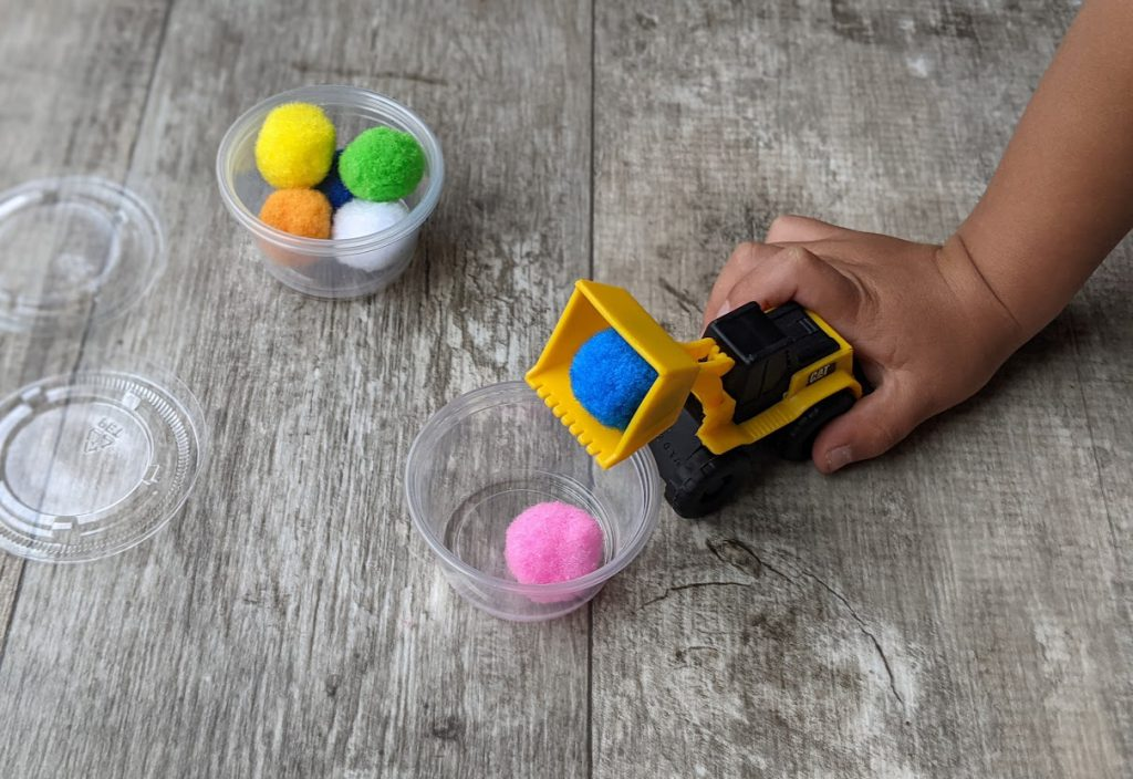 Child putting pom poms into containers with small truck