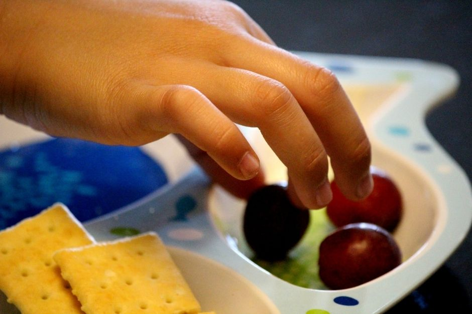 Child picking up grapes from a tray of grapes and crackers