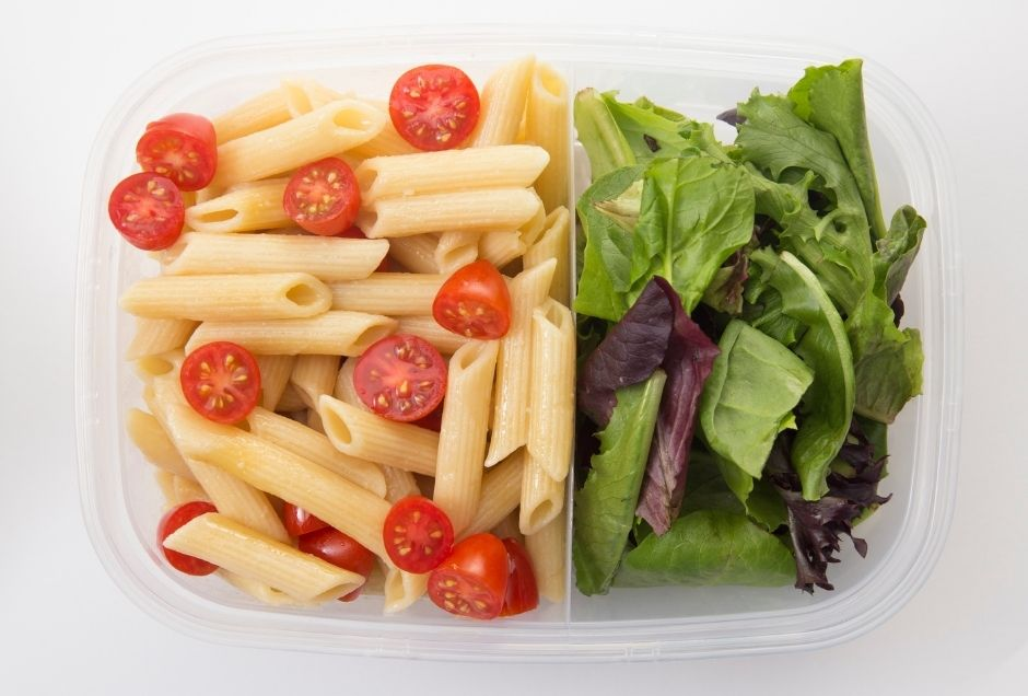 A container packed with pasta salad and green salad