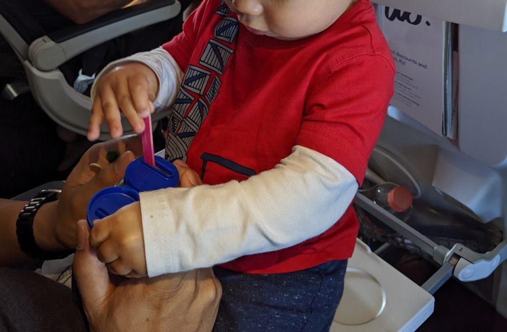 Toddler using a stick jar on a plane