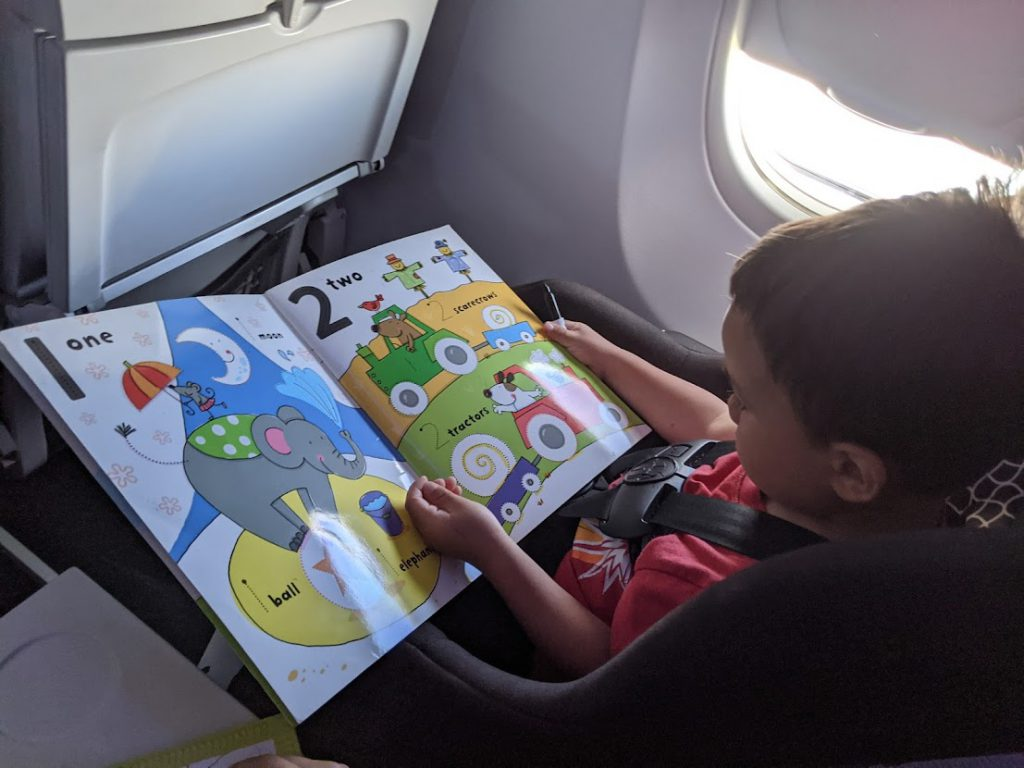 Child drawing on a Wipe Clean book on a plane