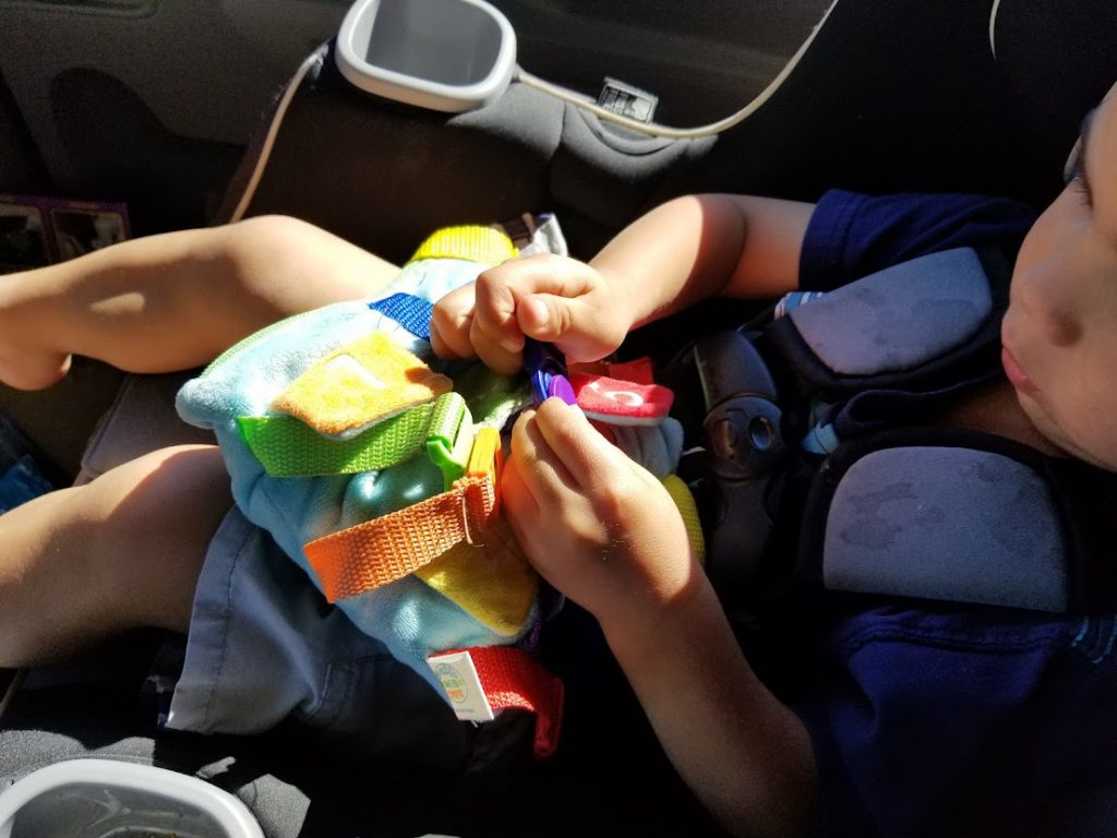 Child playing with a buckle toy in the car- toddler road trip activities