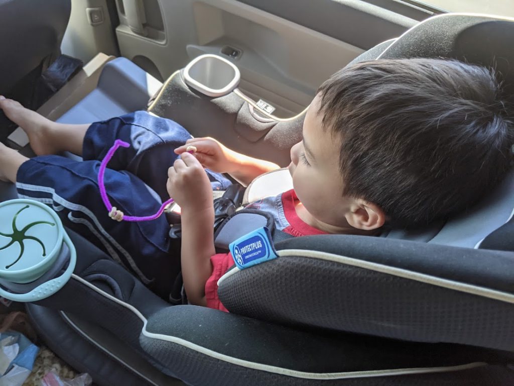 Child putting Cheerios on a pipe cleaner- toddler road trip activities