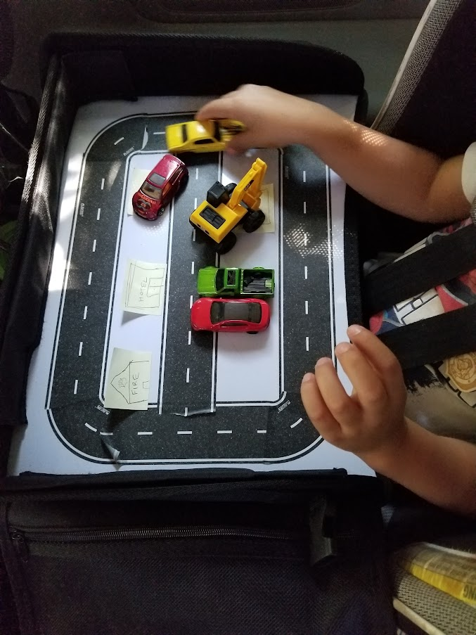 Child playing with cars on a tape road attached to a lap tray in the car