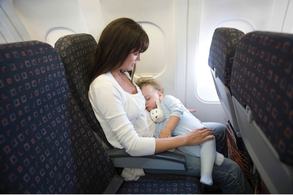 Woman holding a sleeping baby on the plane- first flight with baby