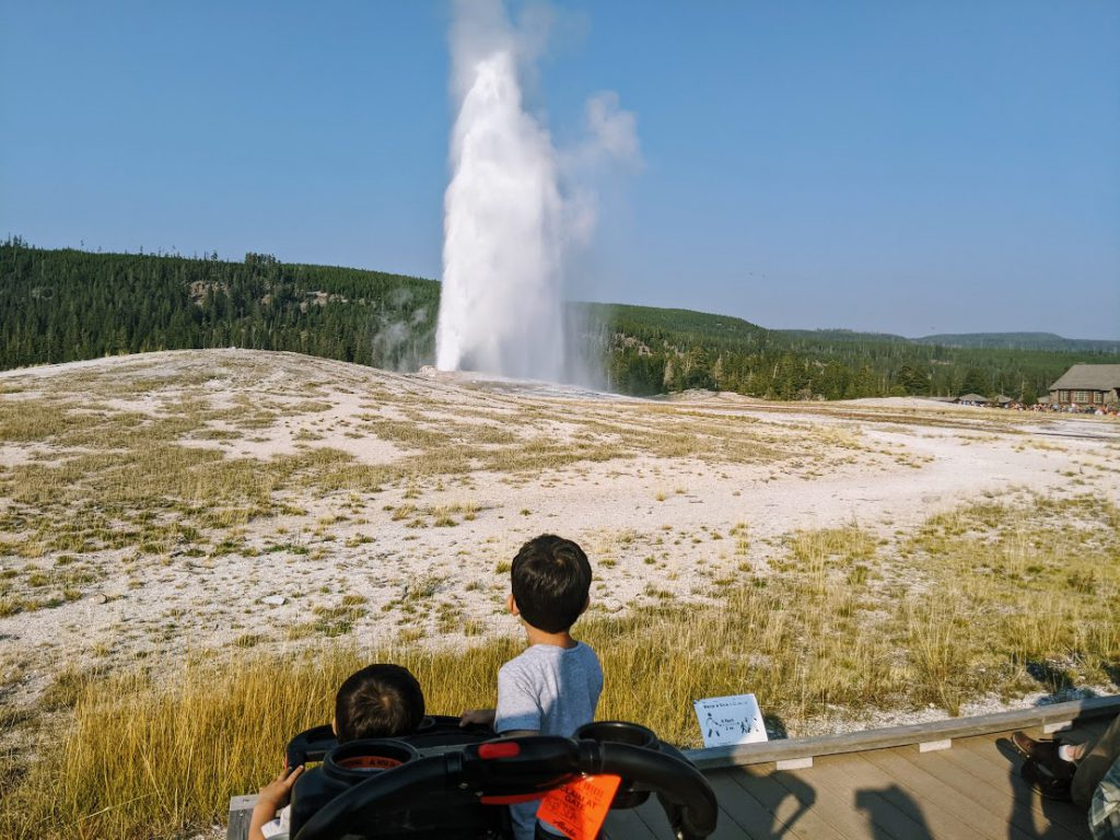 Children watching Old Faithful erupt