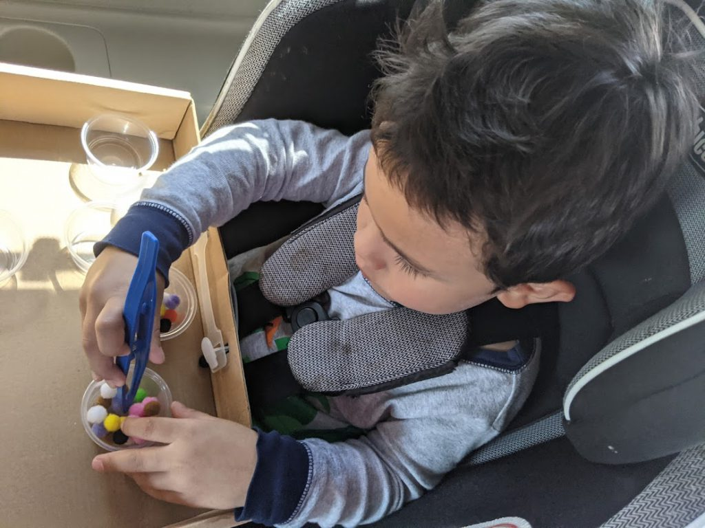 Child using tweezers to move pom poms from one container to another