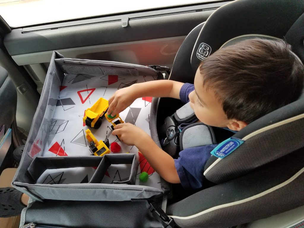 Child playing with miniature trucks in the car- toddler road trip activities