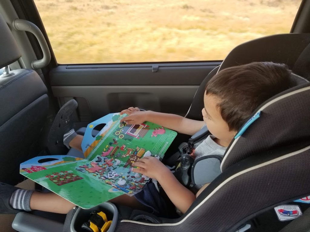 Child  playing with a puffy sticker book- toddler airplane activities