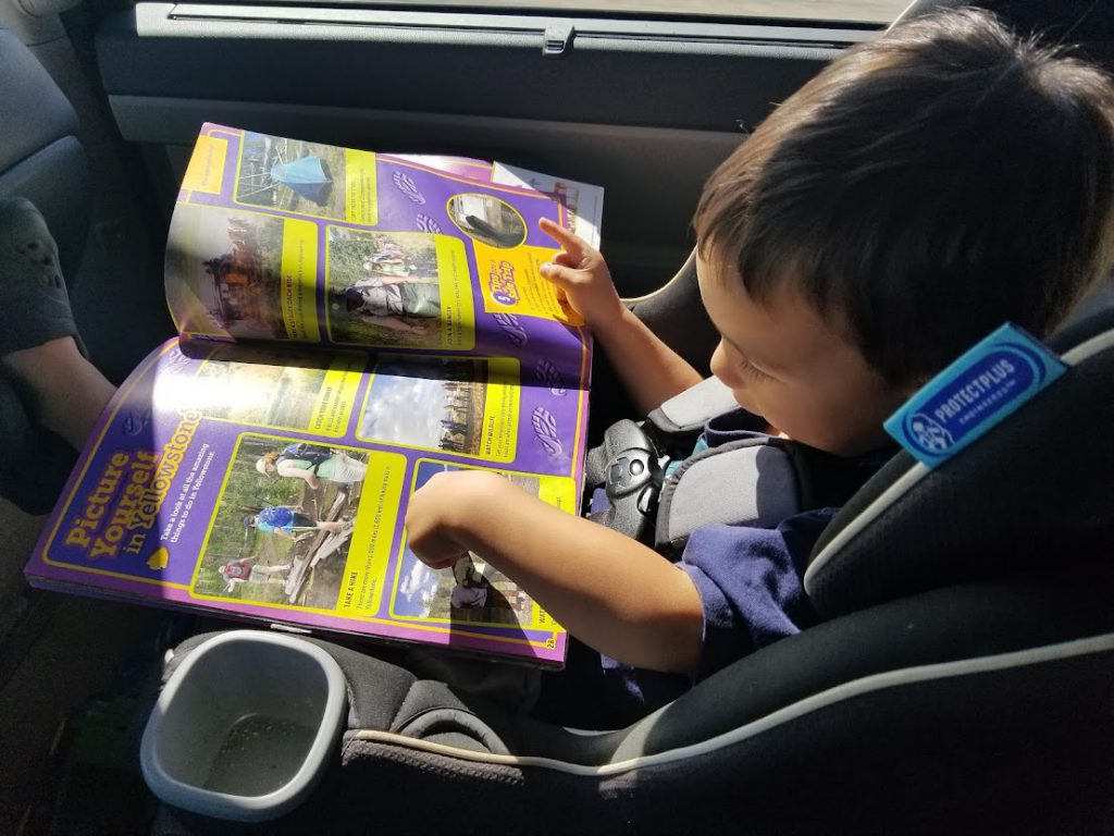 Child reading a book in the car- toddler road trip activities