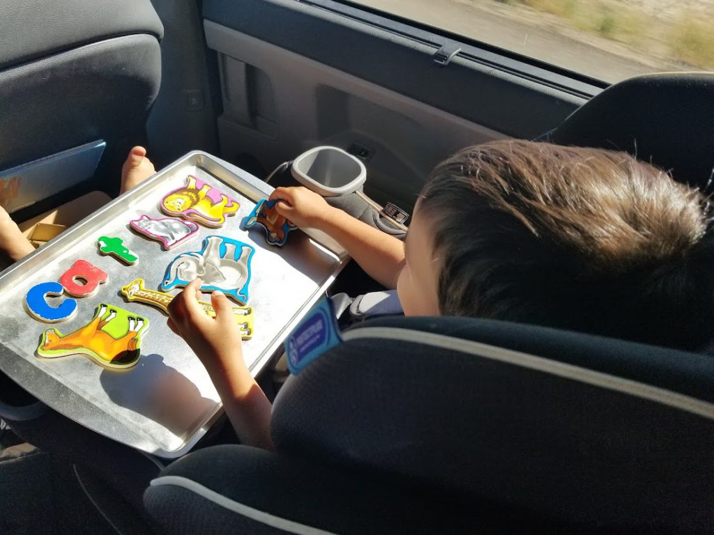 Child putting magnets of letters and animals on a cookie sheet- toddler road trip activities