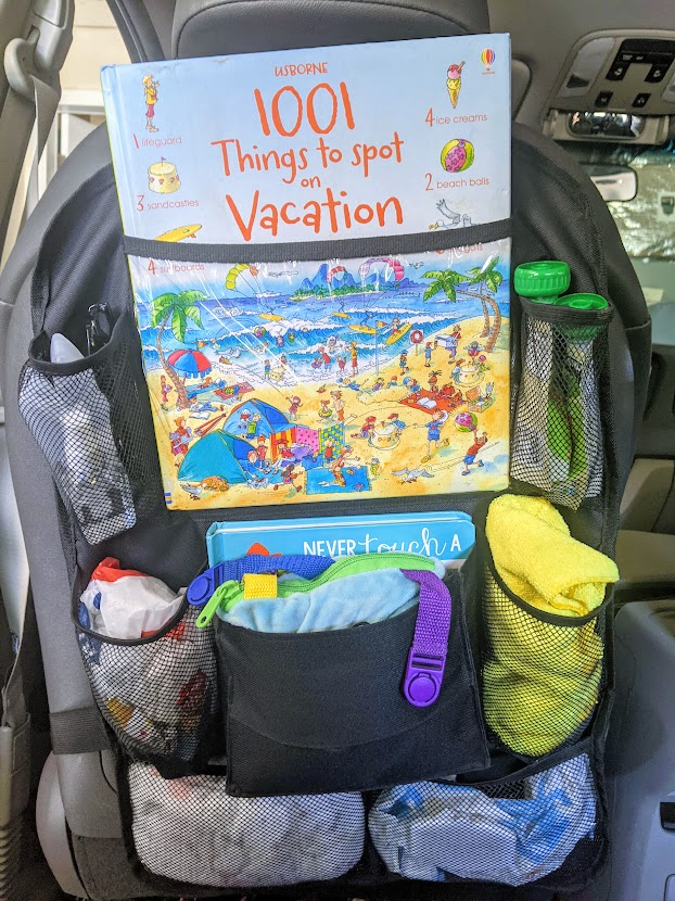 Seat back organizer in a car with kids activities in it- road trip with a toddler