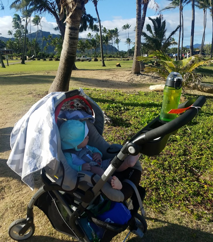 Baby next to the beach in a car seat frame stroller