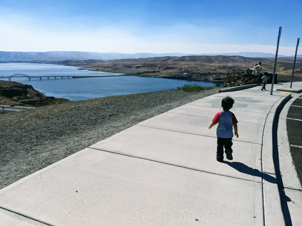 Child running on a sidewalk- road trip with a toddler