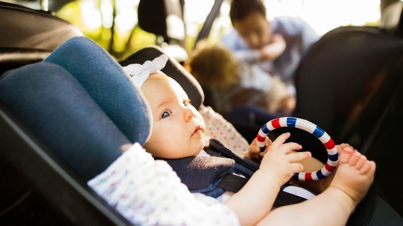 Baby in a car seat in the car- road tripping with a baby
