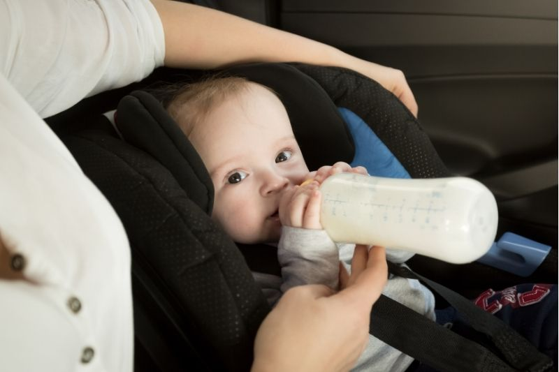 Baby with bottle in car- road tripping with a baby